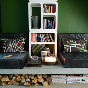 """The reading corner can be turned into an extra bed. Schonning designed the leather poufs himself, and made the cushions from an Ikea carpet. Under the concrete slab there is room for wood, books and newspapers. Photo by <a href=""""http://www.permagnuspersso"""