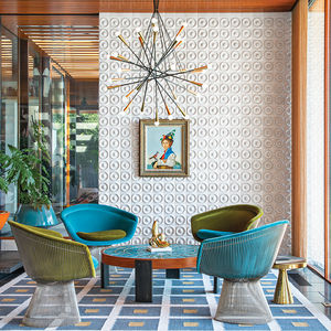 white ceramic tiles cover the back wall while green and blue chair sit around a coffee table with a blue mosaic surface on a rug with a pattern of blue squares