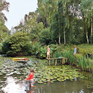 children in a pond and jumping from a dock into the pond