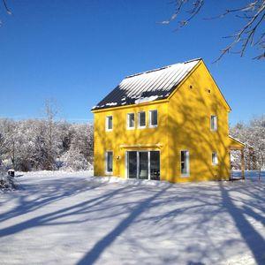 Yellow Passive house that runs on solar power