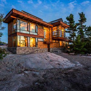 Charles Gane wood cottage exterior at night.