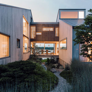 new head of its class connecticut renovation summer home facade bleached cedar siding volumes glass bridge