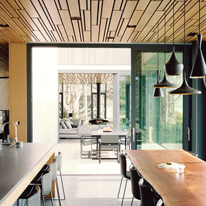 sea change gray basalt tile floor white oak plank ceiling kitchen dining tom dixon pendant lamps