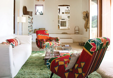 Modern colorful living room with Philippe Xerri chairs and Tunisian rug