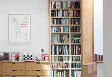 Family room with tall hinged door and wooden bookcases