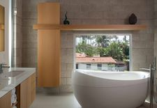 Bathroom with plentiful natural light, concrete walls, and deep tub.