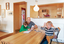 Family sitting on an all wood dining table and chairs