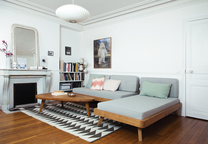 Living room with geometric rug and gray convertible sofa