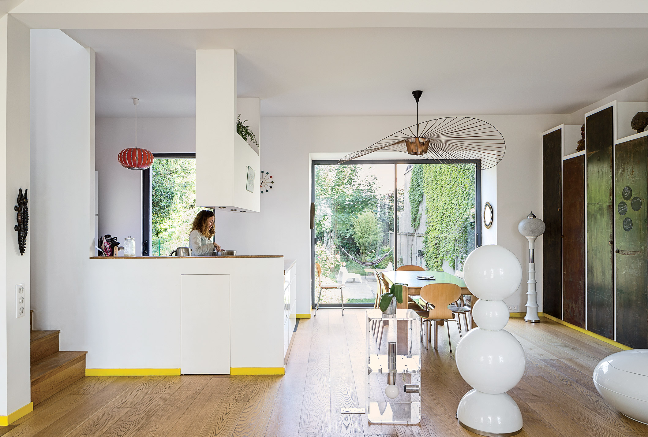 modern prefab home in Paris suburb with Vertigo lamp by Constance Guisset, Gijs Bakker strip table, and metal panels in the living area