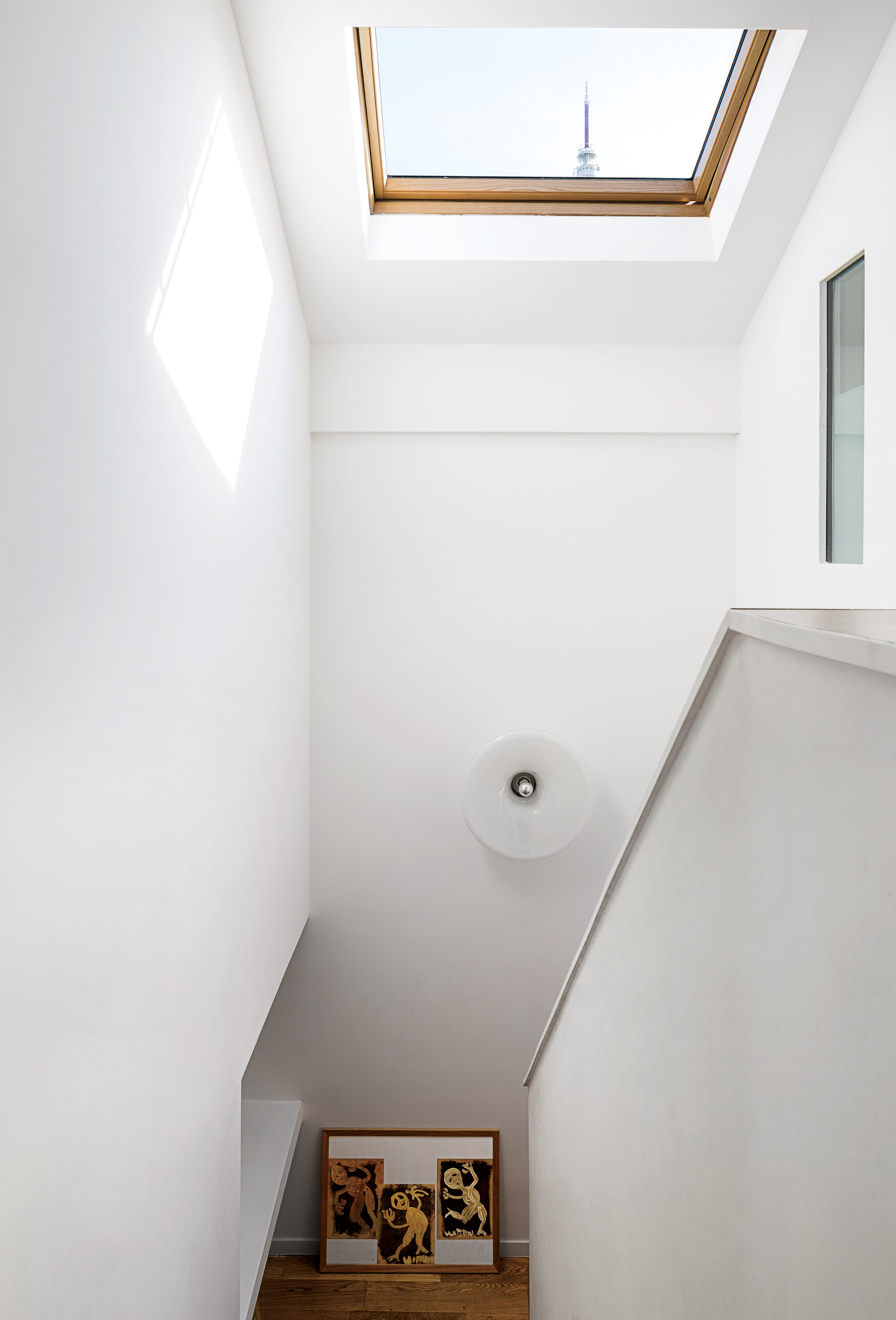 modern prefab home in Paris suburb with Velux skylight and light fixture above staircase